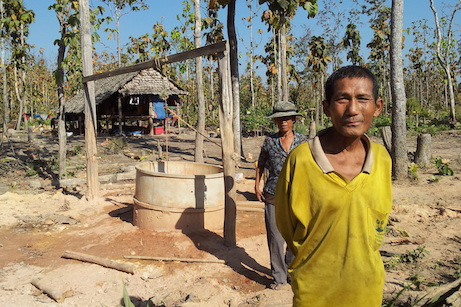 Village man in front of cement well